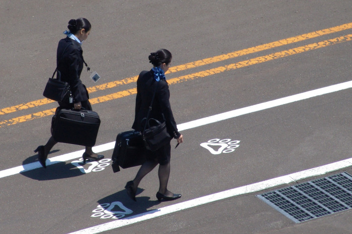 One of the flight attendant requirements: hard work! Two flight attendants walking between terminals. Photo credit: MIKI Yoshihoto